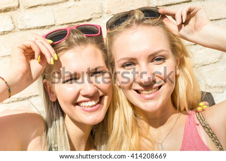 Young fashion women girls taking selfie against stonewall - Summer concept with happy girlfriends having fun together - Best female friends with sunglasses catching moment  - Warm afternoon color tone - stock photo