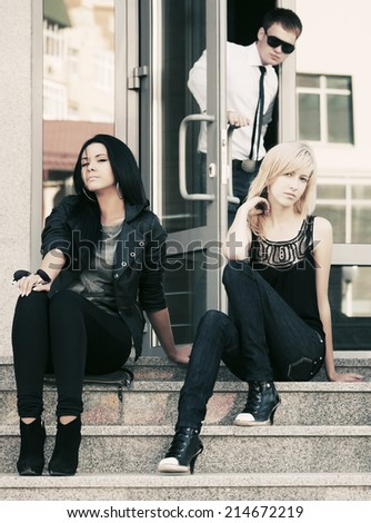 Young fashion women sitting on the steps  - stock photo