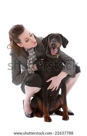 Young fashionable brunette with her doberman pincher on white background - stock photo