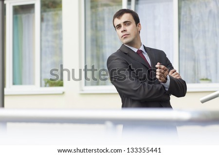 young fashionable businessman standing on the threshold of his office - stock photo
