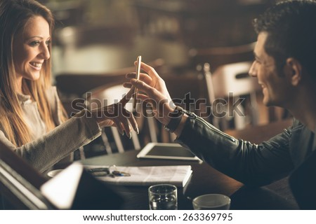 Young fashionable couple at the bar using a mobile touch screen phone - stock photo