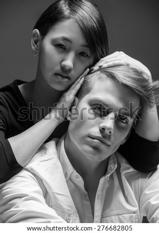 Young fashionable couple dressed casual posing in the studio on dark background. Black and white fashion portrait. Tenderness. - stock photo