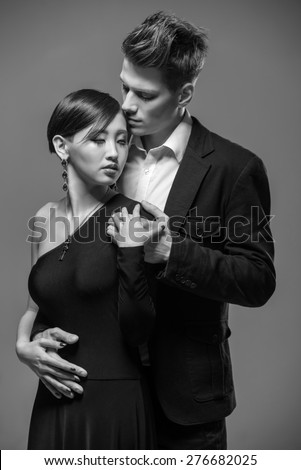 Young fashionable couple dressed in formal clothing posing in the studio. Black and white fashion portrait. Passion.