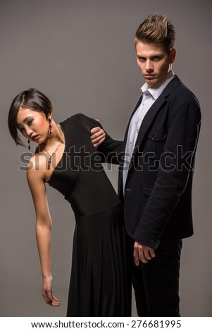 Young fashionable couple dressed in formal clothing posing in the studio on dark background. Fashion portrait. Jealousy. - stock photo
