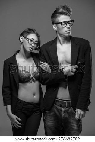 Young fashionable couple in glasses and tuxedos  posing in the studio. Black and white fashion portrait. Passion. - stock photo
