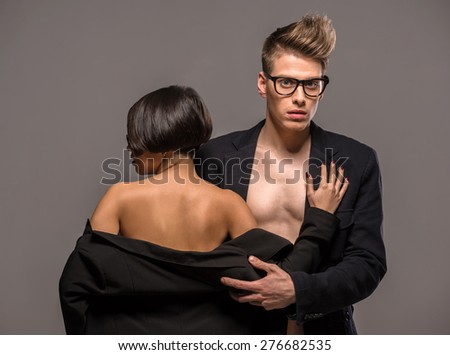 Young fashionable couple in glasses and tuxedos  posing in the studio on dark background. Fashion portrait. Passion.