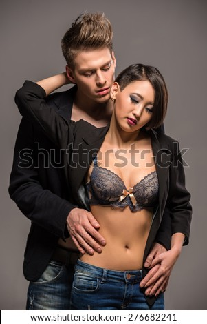 Young fashionable couple in tuxedos posing in the studio on dark background. Fashion portrait. Passion. - stock photo