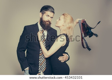 young fashionable couple of woman with pretty face and blonde hair and handsome bearded man with long beard in black jacket and tie in studio on grey background, copy space