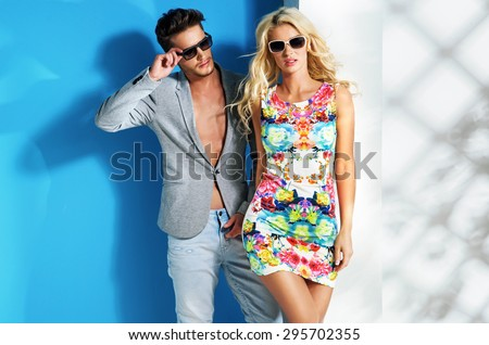 Young fashionable couple on cyan background - stock photo