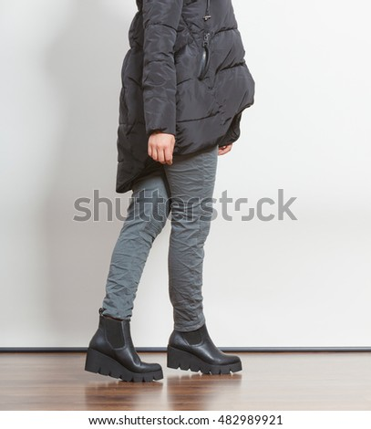Young fashionable girl wearing lemon jacket and shoes on platform. Preparing herself clothes for walk. Fashion in winter time.