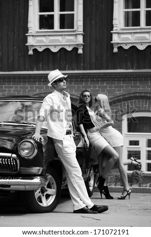 Young fashionable man and women at the retro car - stock photo