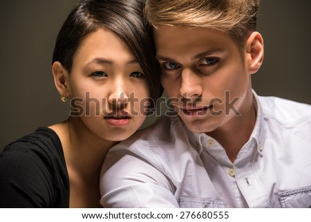 Young fashionable passionate couple dressed casual posing in the studio. Fashion portrait. - stock photo