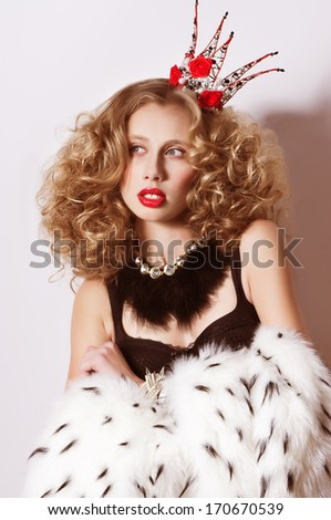 Young fashionable queen with crown and mantle  - stock photo