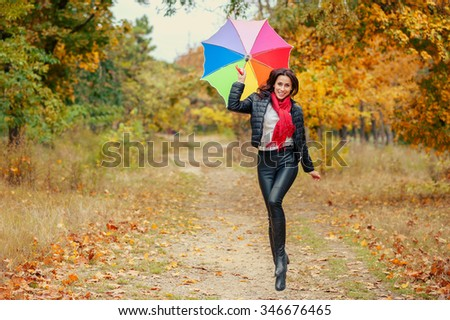 Young fashionable smiling woman with a multi-colored umbrella jumps in the autumn park. Yellow leaves on the background. - stock photo