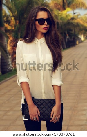 Young fashionable trendy girl posing at tropical alley between palms in evening soft light. Vogue style toned portrait of young woman in black jeans, white blouse and sunglasses holding handbag - stock photo