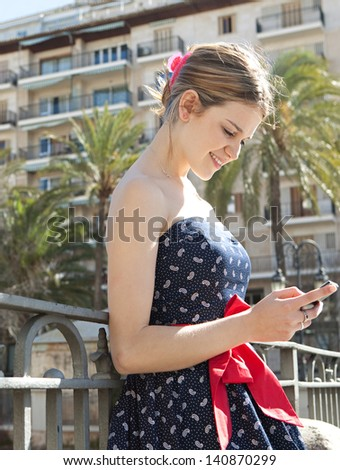 Young fashionable woman holding and using a smarphone to send a message while standing in a city bridge with railings, buildings and palm trees during a sunny day in the summer. - stock photo