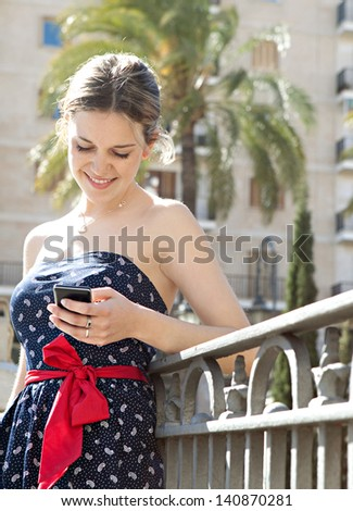 Young fashionable woman holding and using a smartphone to send a message while standing in a city bridge with railings, buildings and street lamps during a sunny day in the summer.