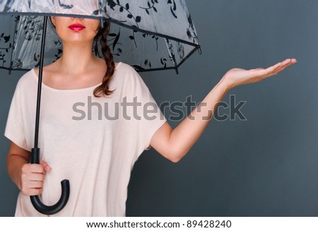 Young fashionable woman holding umbrella standing against grey background - stock photo