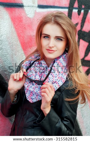 Young fashionable woman in black leather jacket and sunglasses wearing pink scarf and smiling - stock photo