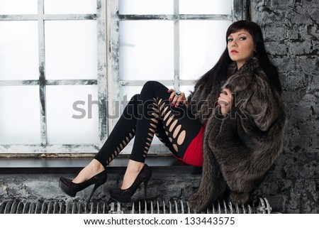 Young fashionable woman in fur coat posing on a window sill - stock photo