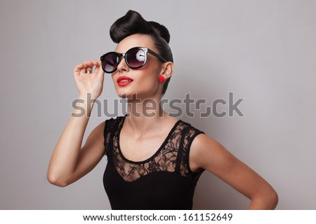 Young fashionable woman in round sunglasses posing in guipure dress. Red lips. Updo, twisted high bun. top knot - stock photo