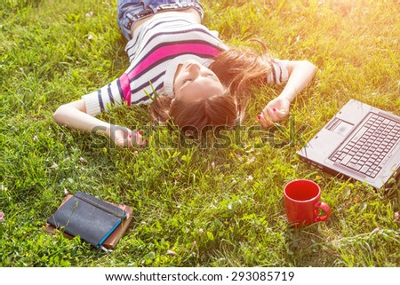 Young fashionable woman relax after work with laptop in city park - stock photo