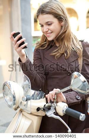 Young fashionable woman standing by her motorbike in the city, holding and using a smartphone cell mobile, smiling in town. - stock photo