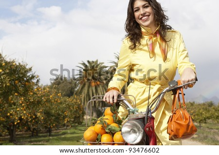 Young fashionable woman standing with a motorbike and a shopping basket full of oranges, in an orange grove. - stock photo