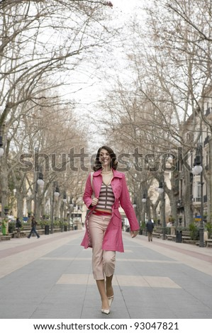 Young fashionable woman walking down a pedestrian street. - stock photo