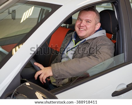 Young fat man behind wheel. Smiling Caucasian man      - stock photo