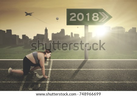 Young fat woman kneeling on the start line with numbers 2018 on the signpost