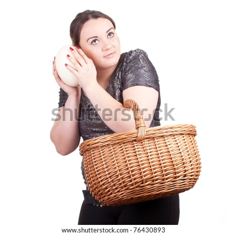 young fat woman with ostriches egg and wicker basket - stock photo
