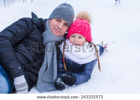 Young father and adorable little girl on skating rink outdoor - stock photo