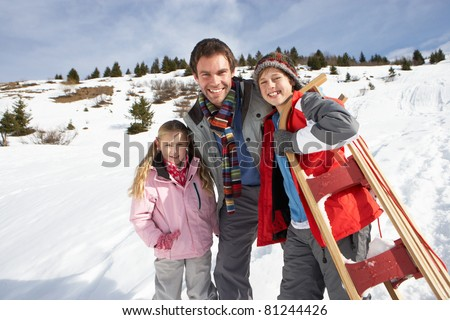 Young Father And Children In Snow With Sled