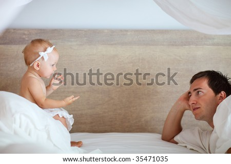 Young father and cute baby girl talking with each other in bed