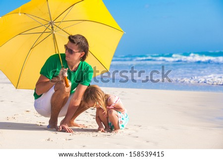 Young father and his adorable little daughter hiding from the sun under a yellow umbrella on white sunny day - stock photo