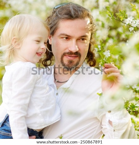 Young father and his adorable toddler daughter having fun in blossoming cherry garden on beautiful spring day - stock photo