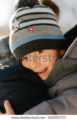 Young father and his child having fun in winter park on a bright day hugging each other and smiling  - stock photo