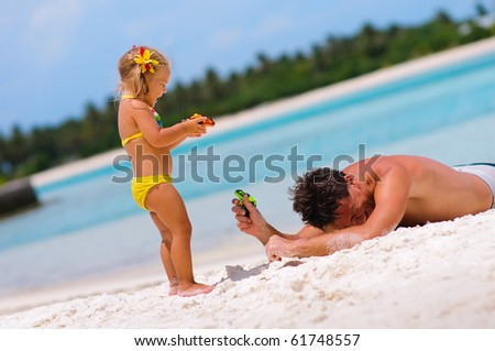 young father and his cute little daughter playing with water guns on exotic beach - stock photo