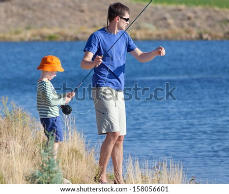 young father and his cute son fishing together - stock photo