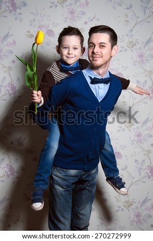 young father and his cute son with yellow flower in his little hand. happy blue-eyed kid. man which is proud of the son - stock photo