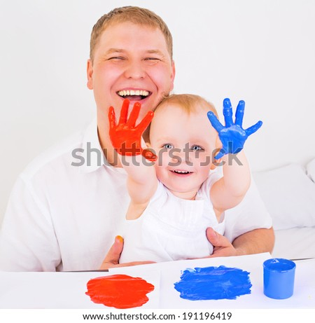 young father and his daughter playing with fingerpaints at home - stock photo