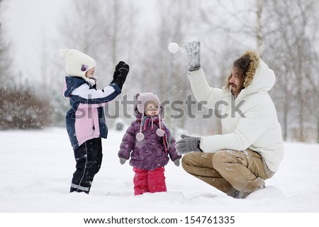 Young father and his daughters having fun on winter day - stock photo