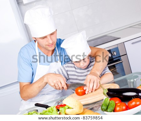 young father and his five year old son cook together in the kitchen at home - stock photo