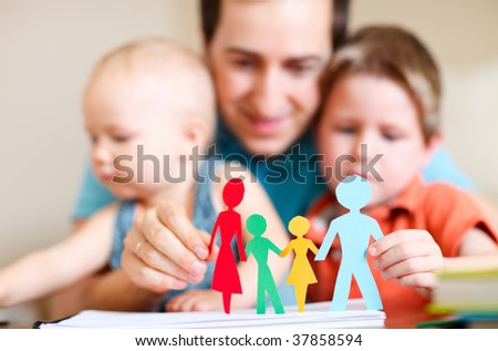 Young father and his kids holding figures of multicolored paper family - stock photo
