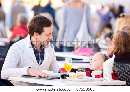 Young father and his little daughter at outdoor cafe on autumn day