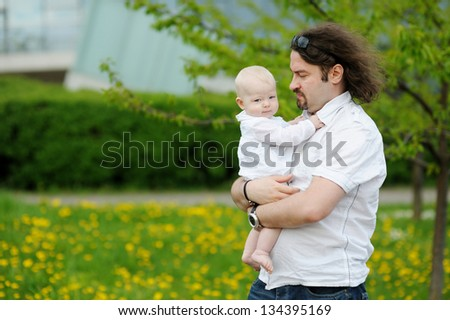 Young father and his little daughter at summer