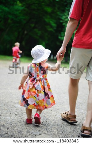 Young father and his little daughter walking in the park. Little  son is riding a bicycle - stock photo