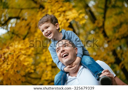 Young father and his little son enjoy outdoors in a park. Father holding his son on the shoulders. Selective focus on kid face. - stock photo