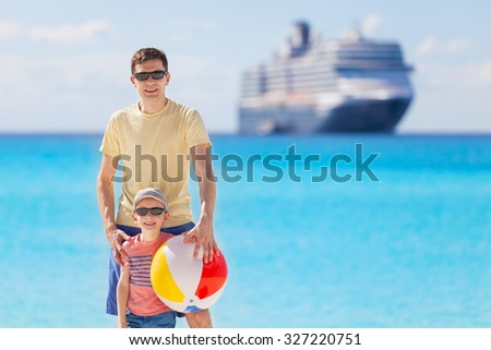 young father and his little son enjoying beach vacation and playing with beach ball, cruise and beach vacation concept - stock photo